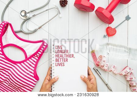 Woman's Hands Holding Book, Fitness Equipments And Stethoscope On White Wooden Background, Top View,