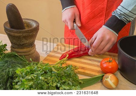 Young Male Cooking Healthy Meal In The Kitchen. Cooking Healthy Food At Home. Man In Kitchen Prepari