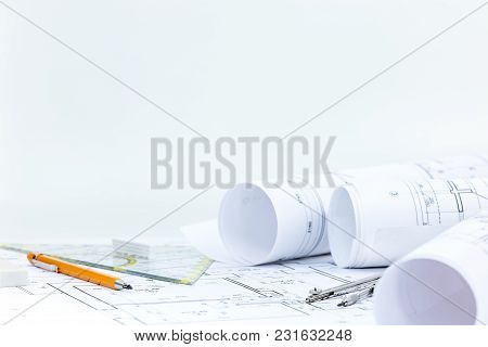 Workplace Of Architect. Blueprint Rolls And Plans With Drawing Tools On Desk.