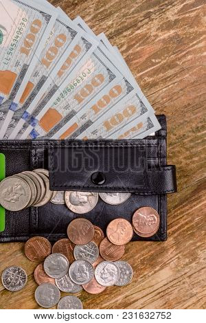 One Hundred Dollars Banknote Reach Out Out Of A Black Old Purse. And Also Different Coins Are Us Cen