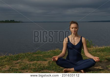 Young Girl In Blue Sportswear Meditating Outdoor