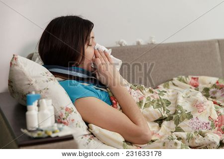 Young Woman With A Cold. Sits On A Bed In A Blanket