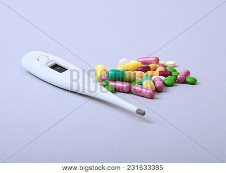 Pills And Medical Thermometer On White Background. Medical Background