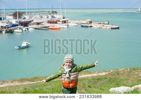 Dreamy Caucasian Little Kid In Jacket And Hat Stands On Green Hill Spreading His Hands Like Wings On