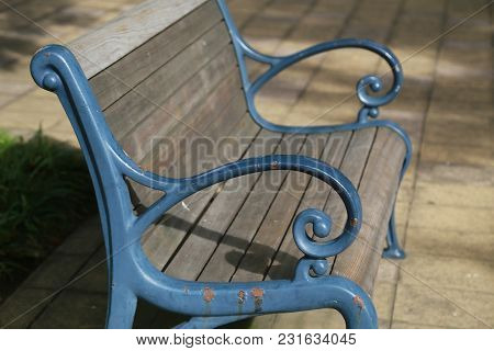 A Sight Of A Blue Bench In A Sunny Park