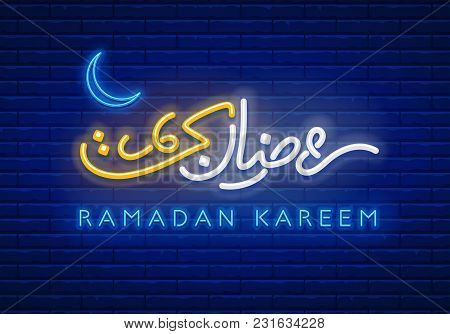 Neon Sign Ramadan Kareem With Lettering And Crescent Moon Against A Brick Wall Background. Arabic In