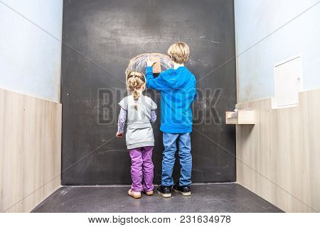 Happy Boy And Girl Using Chalkboard In The Classroom