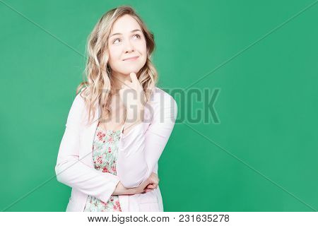 Adorable Thoughtful Blonde Woman Looks Upwards, Poses Against Green Background With Copy Space For Y