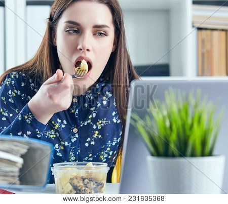 Business Woman Eating Lunch At Her Workplace.