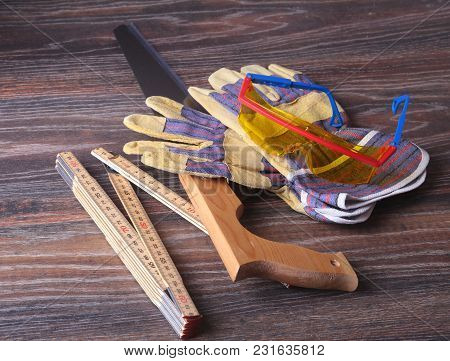 Orange Hard Hat, Safety Glasses, Gloves, Saw And Measuring Tape On Wooden Background. You Can Place