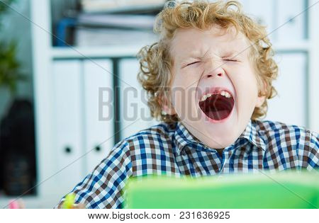 Tired Schoolboy Yawn Sitting At The Table In Class At The Lesson. Large Number Of Lessons And Homewo