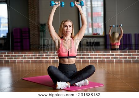 Slim Young Woman With Long Blond Hair With Intense Expression Lift Up Dumbbells While Sitting On Spo