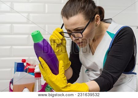 Housewife Woman Does The Cleaning With Interest Reading The Instructions On The Detergent.