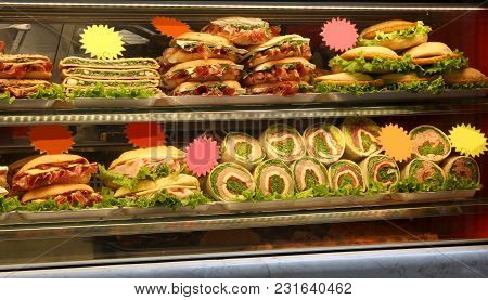 Showcase With Many Sandwiches  With Ham Cheese Lettuce And More Ingredient For Sale At Bar