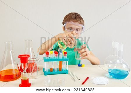 Young Boy In Safety Goggles Doing Chemical Experiments In The Laboratory