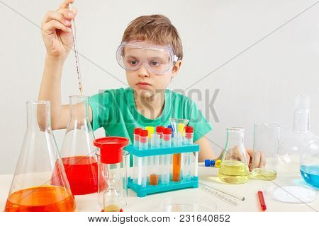 Little Serious Boy In Safety Glasses Doing Chemical Experiments In The Laboratory