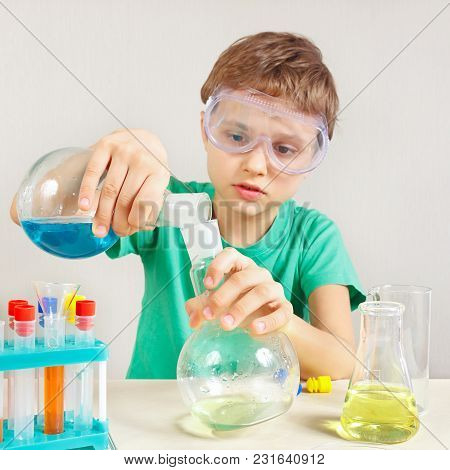 Young Boy In Safety Goggles Studies Chemical Practice In The Laboratory