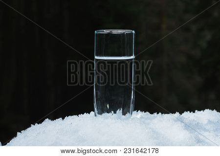 A Transparent Glass Glass With Drinking Mountain Water Stands In The Snow Against A Background Of A
