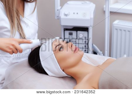 The Cosmetologist Makes The Procedure Microcurrent Therapy Of The Facial Skin Of A Beautiful, Young