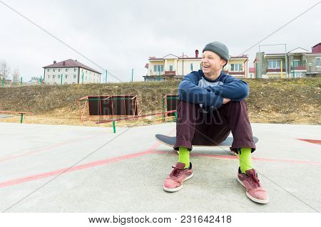 A Teenage Boy Is Sitting On A Skateboard In The Park And Smiling. The Concept Of Free Time Pastime F