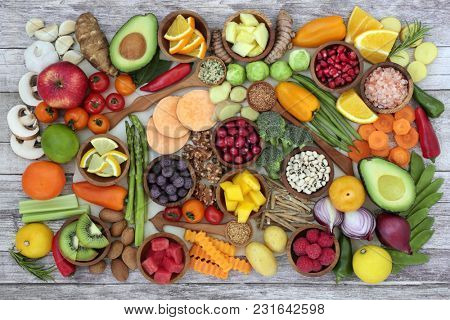 Health food concept with fruit, vegetables, herbs, spice, nuts, seeds, grain and pulses. Super foods high in antioxidants, anthocyanins, fibre, protein, smart carbohydrates, vitamins and minerals.