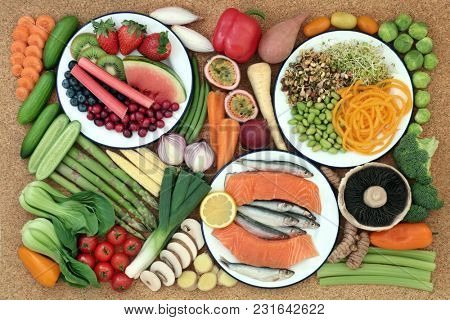 Health food for healthy eating concept with fresh fish, vegetables and fruit on cork background. Healthy food concept high in omega 3, antioxidants, anthocyanins, minerals, vitamins and dietary fibre.