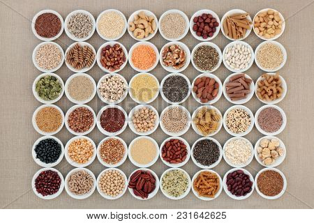Vegan high protein dried super food selection with nuts, seeds, legumes, cereals and grains. Health foods high in fibre, antioxidants, anthocyanins, minerals and vitamins. On hessian, top view.