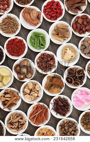Chinese herbal medicine with traditional herbs iin white porcelain bowls on marble background.Top view.
