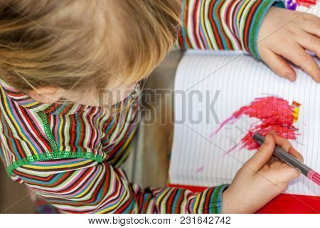 Top View Of Little Girl Painting In A Book.