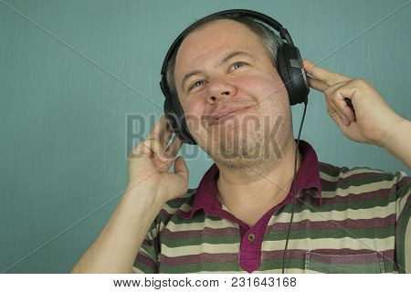 Man Listening To Music In Big Headphones While Sitting By Their Hand And Smiling With Pleasure On A