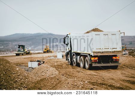 Industrial Dumper Trucks Working On Highway Construction Site, Loading And Unloading Earth. Heavy Du