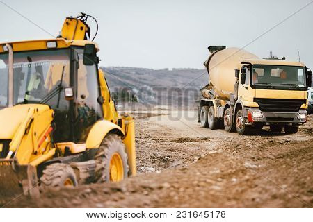 Industrial Backhoe Excavator Machinery And Cement Truck On Road Construction Site