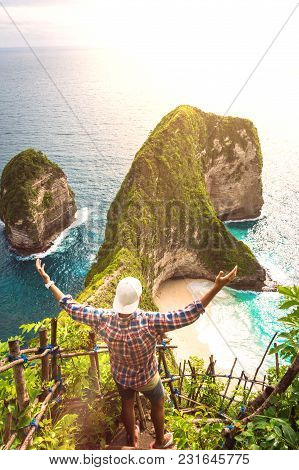 Man Standing With Raised Hands On A Cliff Of Kelingking Beach On Nusa Penida Island, Indonesia