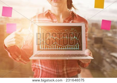 Unrecognizable Businesswoman Pointing At Laptop With Business Chart On Blurry City Background With S