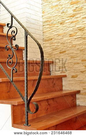 Wooden Interior Stairway With Ornamental Ironwork Railing And Stone Tiles On The Wall In The Backgro