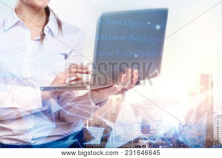 Businesswoman Hands Using Laptop Computer On Abstract City Background With Glowing Digtal Interface.