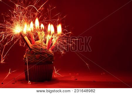 Muffin With Cream In A Lot Of Candles And Bengal Lights