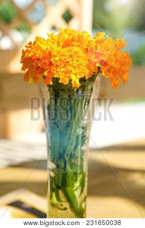 Flowers In Vase On A Wooden Table Outdoors