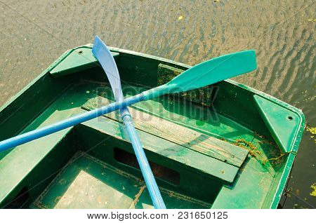 An Old Wooden Boat With Two Oars