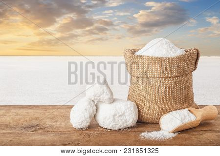 Salt In Bag. Crystals Of Salt In Sack On Table With Salty Lake In The Background. Bag Of Sea Salt Pr