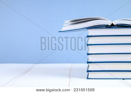A Stack Of Books On A Blue Background. One Hidden Book On Top Of The Pile