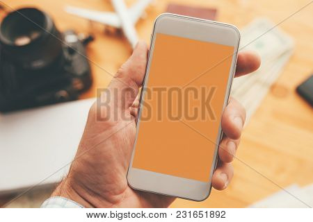 Travel App For Mobile Phone Mock Up Screen, Overhead View Of Male Hand Using Smartphone With Blank S