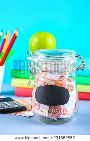 Bank With Russian Money, 5000 Rubles And A Calculator, Books On A Gray Background. Finance, Moneybox