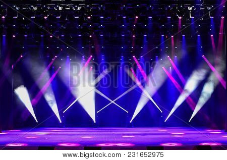 Illuminated Empty Concert Stage With Haze And Rays Of Red, Purple And Blue Light. Background For Mus