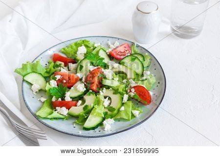 Fresh Salad With Sliced Avocado, Tomatoes, Cucumbers And Greek Feta Cheese On White With Copy Space.