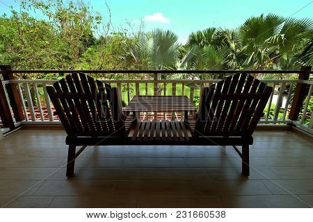 Couple Of Wooden Chairs At Balcony Terrace Facing The Beautiful Green Garden And Blue Sky At Daytime