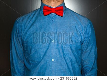 Young And Handsome Hipster Man In Blue Jeans Shirt And Red Bow-tie Over Vintage Background