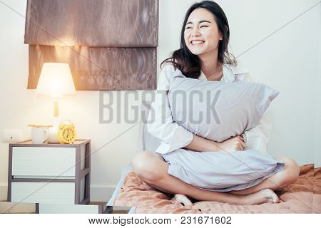 Asian Girl Who Just Wake Up In The Morning As Relaxed And Smiling. She Opened The Window To Receive