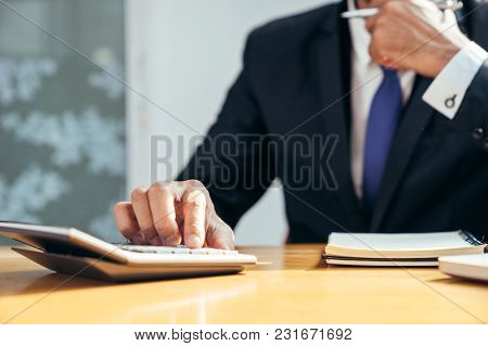 An Asian Businessman Press The Calculator Button On His Working Desk By Close-up His Right Hand, Bus