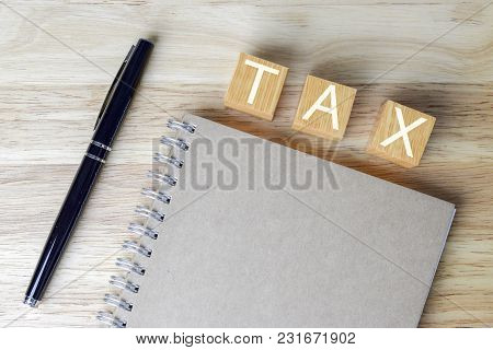 Growing Taxes - Wood Blocks With Tax And Book On Table - Tax Concept